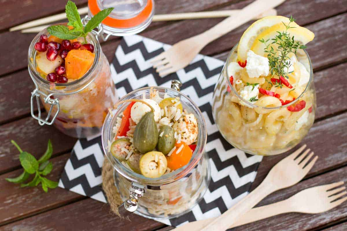 Assorted jars filled with salad on a picnic table.