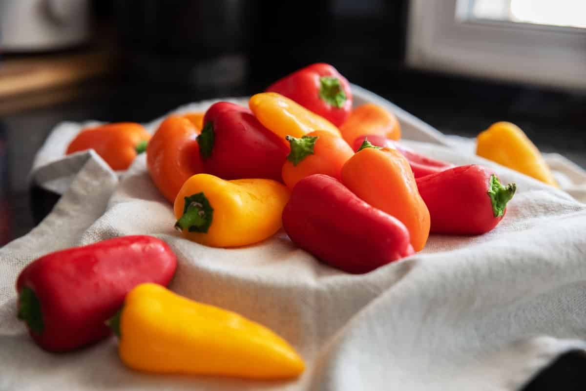 Small fresh peppers of assorted colours, red, yellow, and orange.