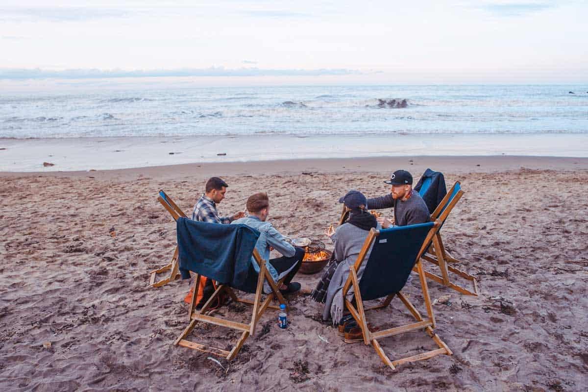 Group of friends on a beach around a bonfire.