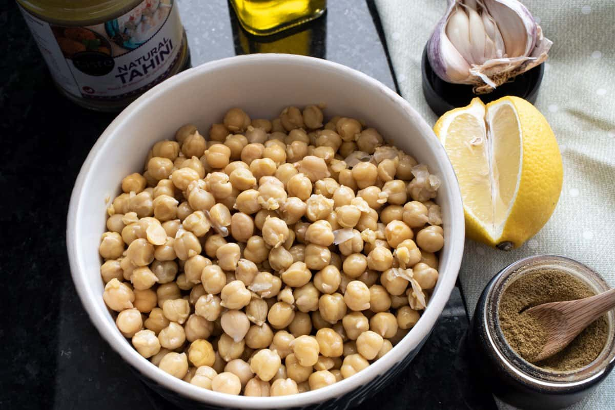 Bowl of chickpeas and ingredients for hummus.
