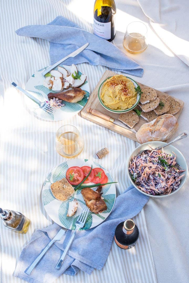Romantic picnic layout with smoked chicken, coleslaw and hummus dip.