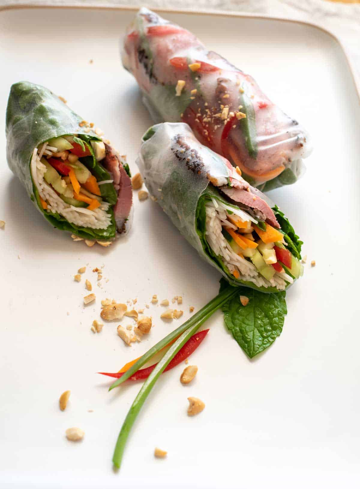 Plate of smoked duck rice paper rolls with one cut on the angle.