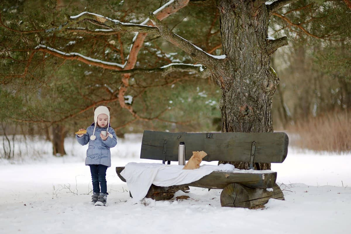 Small girl in the snow next to a picnic bench having picnic lunch.