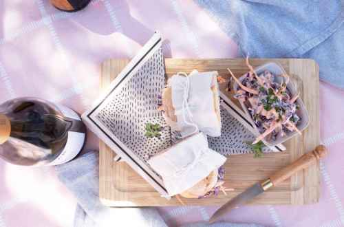 Coleslaw and Baguette sandwich halves wrapped in paper and tied with string on a picnic blanket.