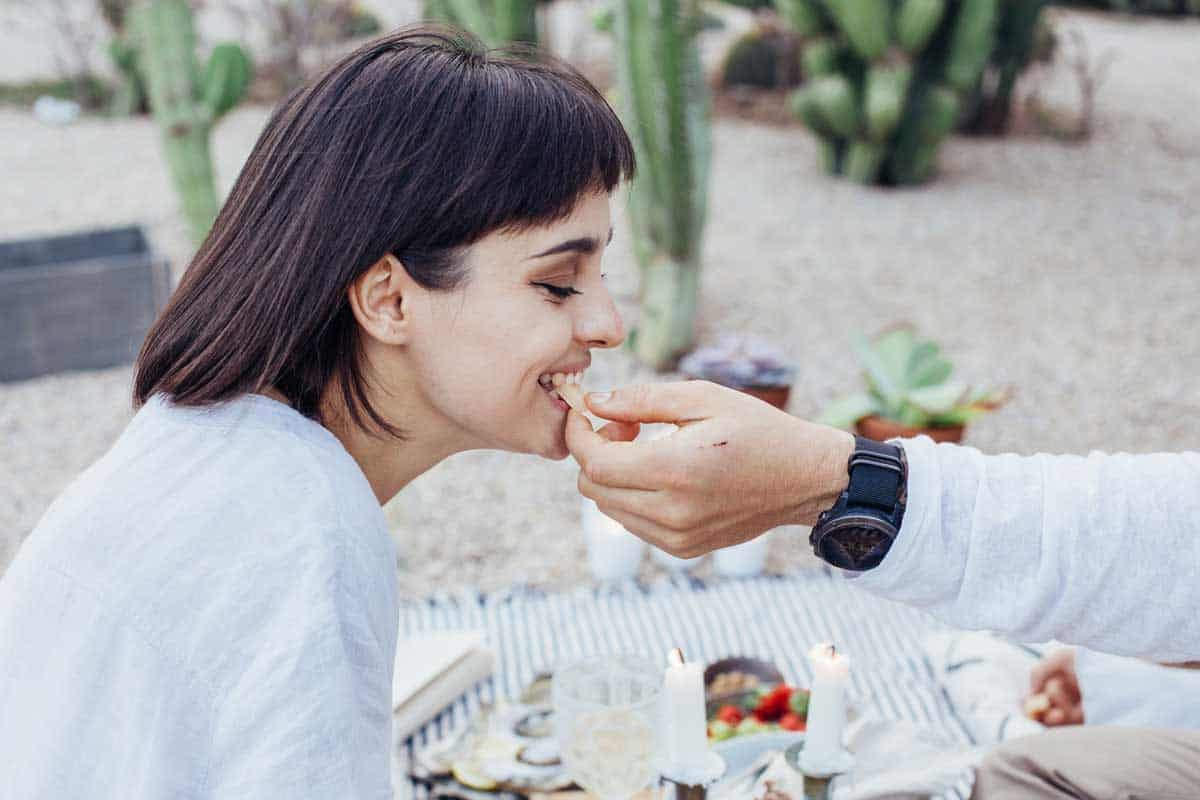 Girl being fed a snack by her boyfriend at a picnic.