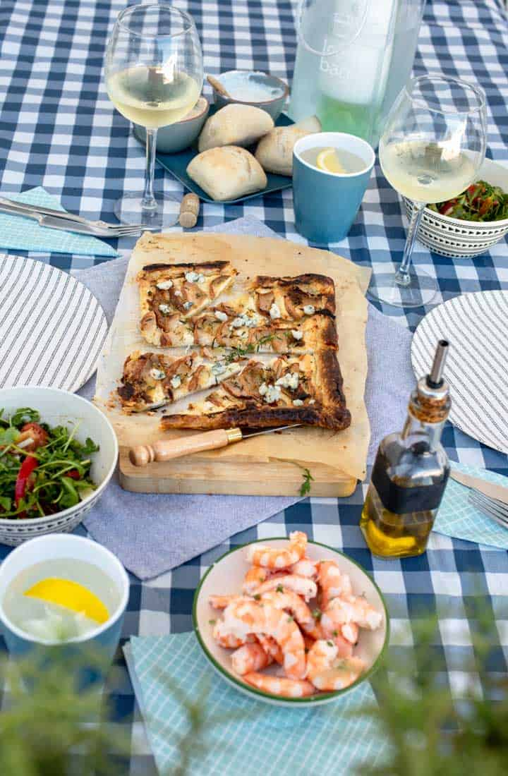 Picnic spread on blue and whicte check table cloth with prawns, salad and pear tart.