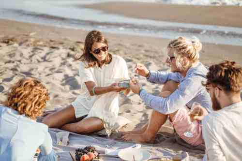 Attractive couple enjoying a picnic with friends on the beach.