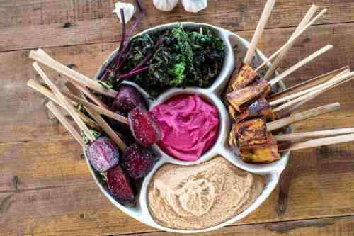Brightly coloured platter of assorted dips with vegetable skewers.