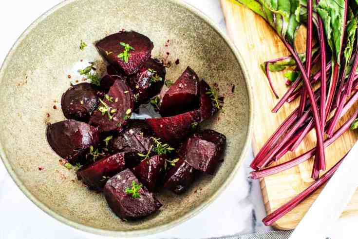 Roasted beets in a bowl with the beetroot leaves scattered around.