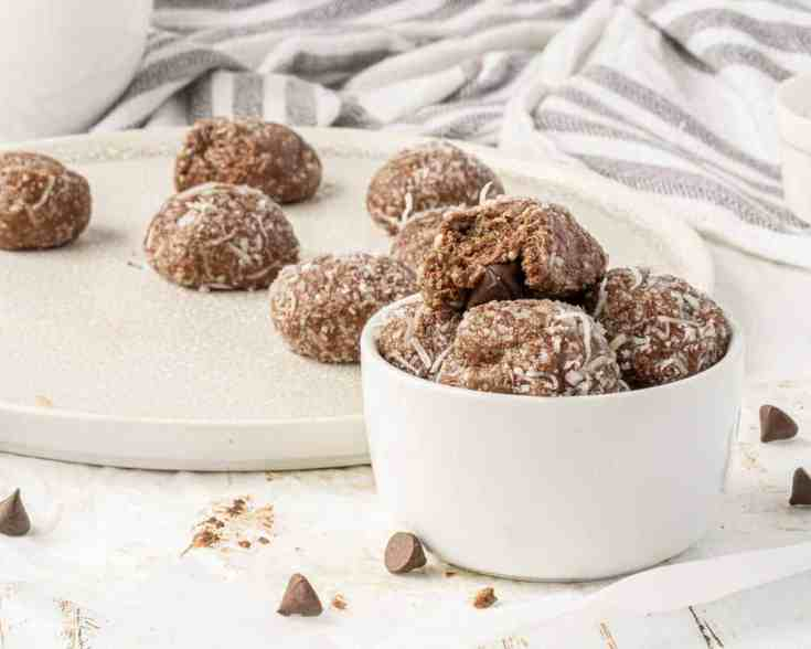 Cocoa peanut butter fat bombs in a small serving bowl and laid out on a plate.