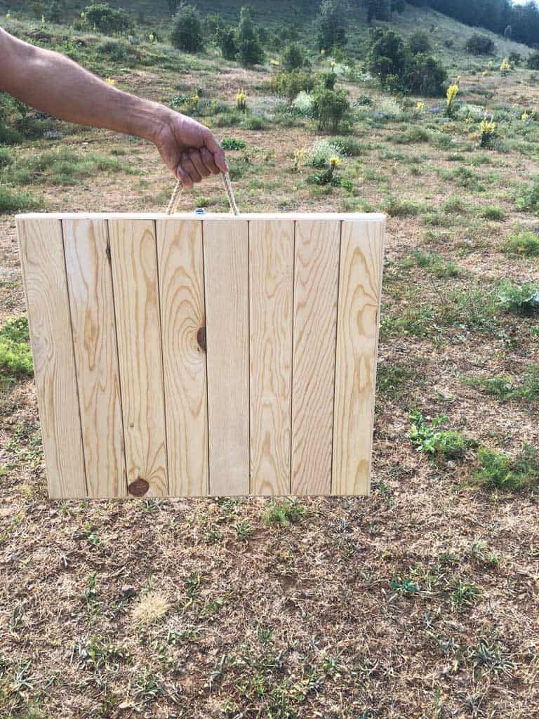 Hand carrying a wooden foldable picnic table demonstarting the folded position.
