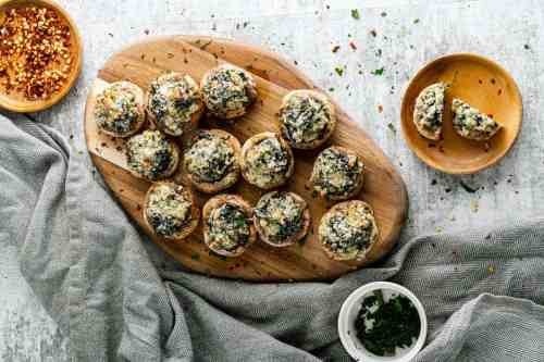 Wooden platter of cooked stuffed mushrooms.
