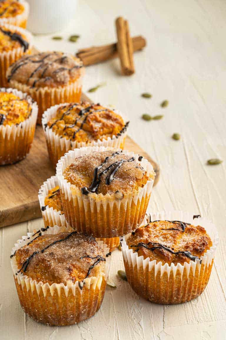 Low carb pumpkin muffins displayed on a serving board with pumpkin seeds scattered around.