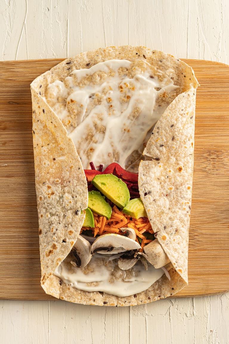 Demonstrating the tortilla wrap of raw veggie wraps.