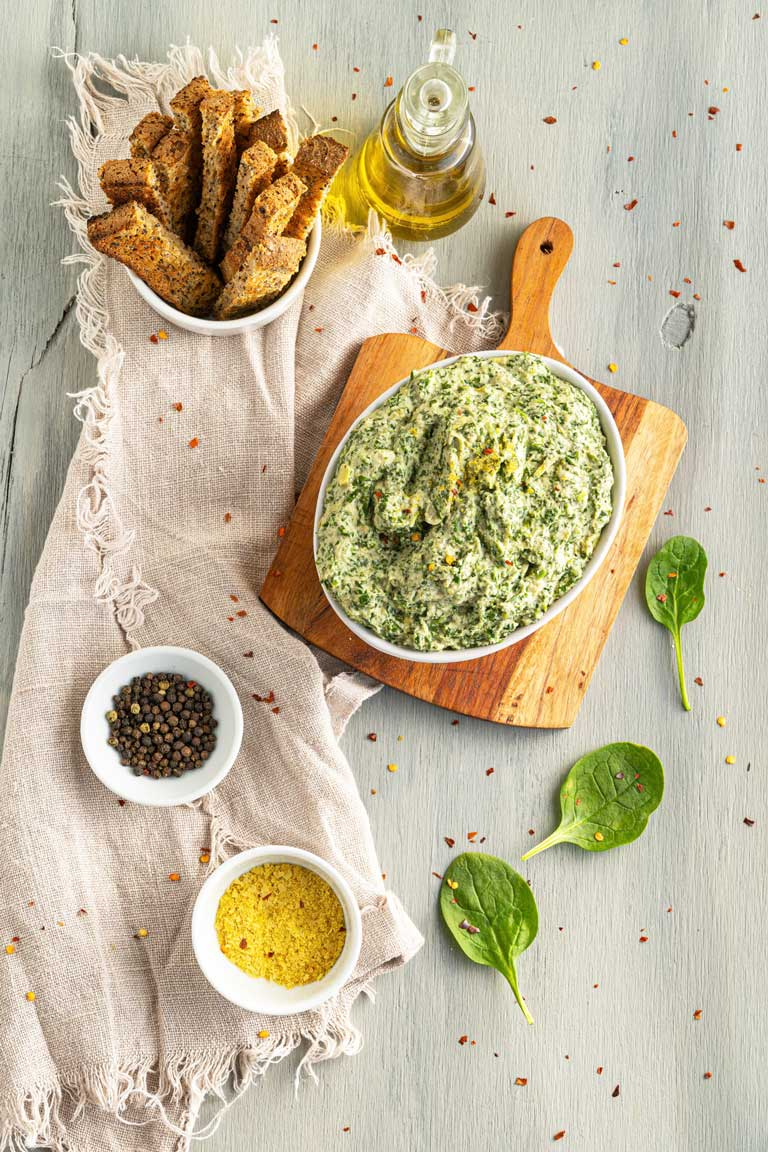 Vegan spinach dip on a board displayed with ingredients and dipping toasts.