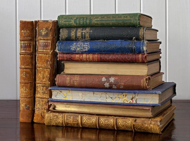 Old books with beautiful, colourful, and decorative bindings on antique wood bench