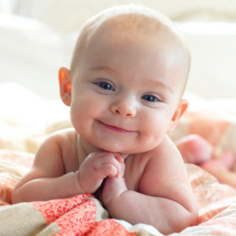 Cute Baby Laying On Bed Smiling Face