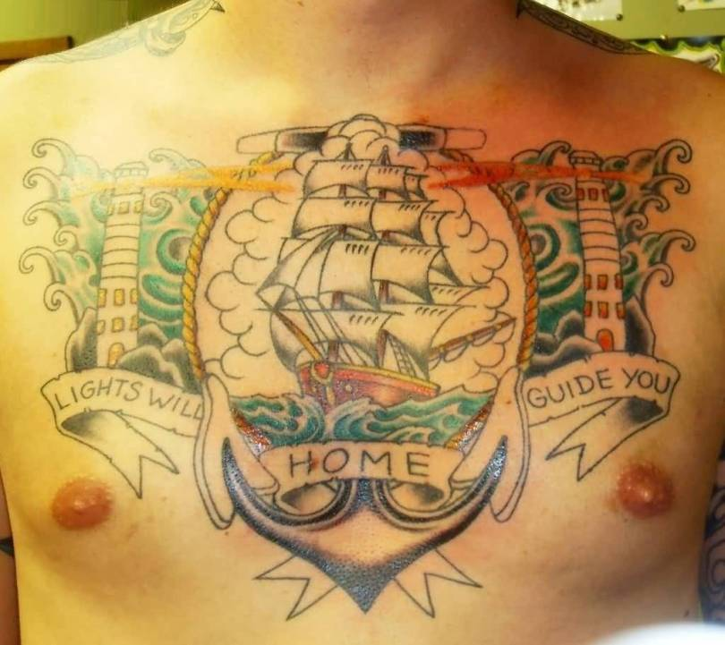 beautiful red and green color ink anchor tattoo on boy's chest with roses