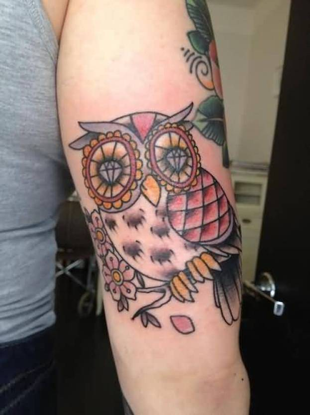 brilliant red black and yellow color ink animated owl tattoo on boy's sleeve for boys only made by expert