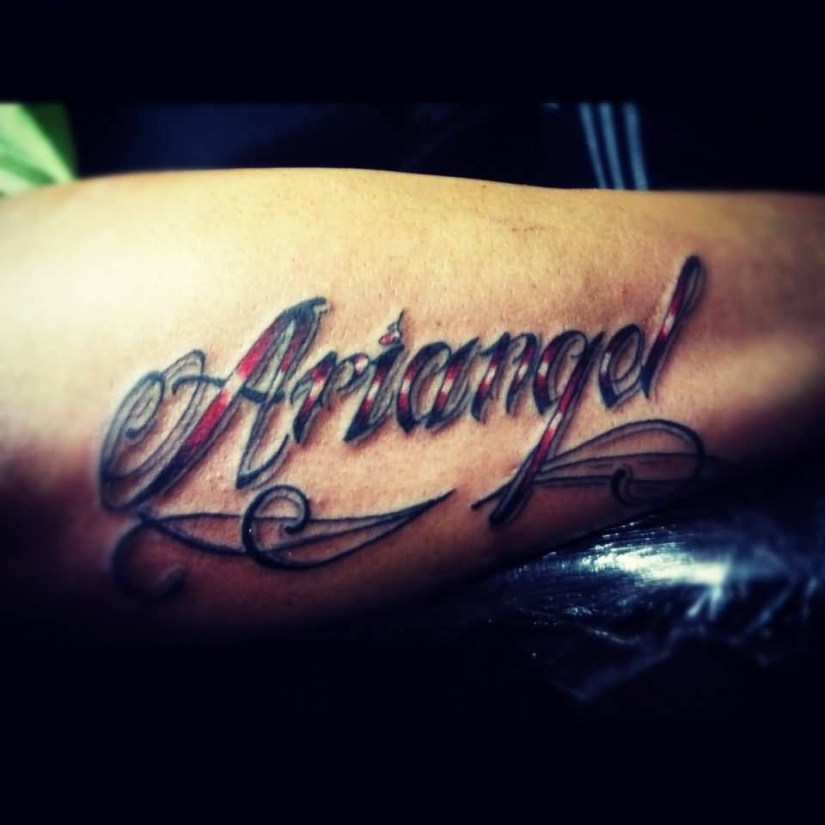 terrific red and blue color ink ambigram word tattoo on forearm for man made by expert
