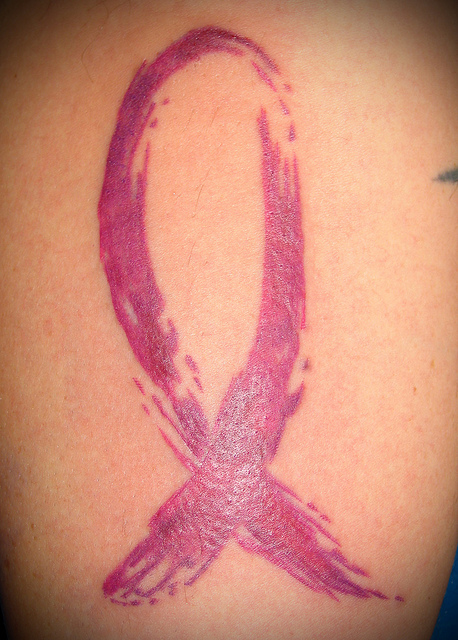 Awesome Pink Color Ink Breast Cancer Ribbon Tattoo On Back For Girls