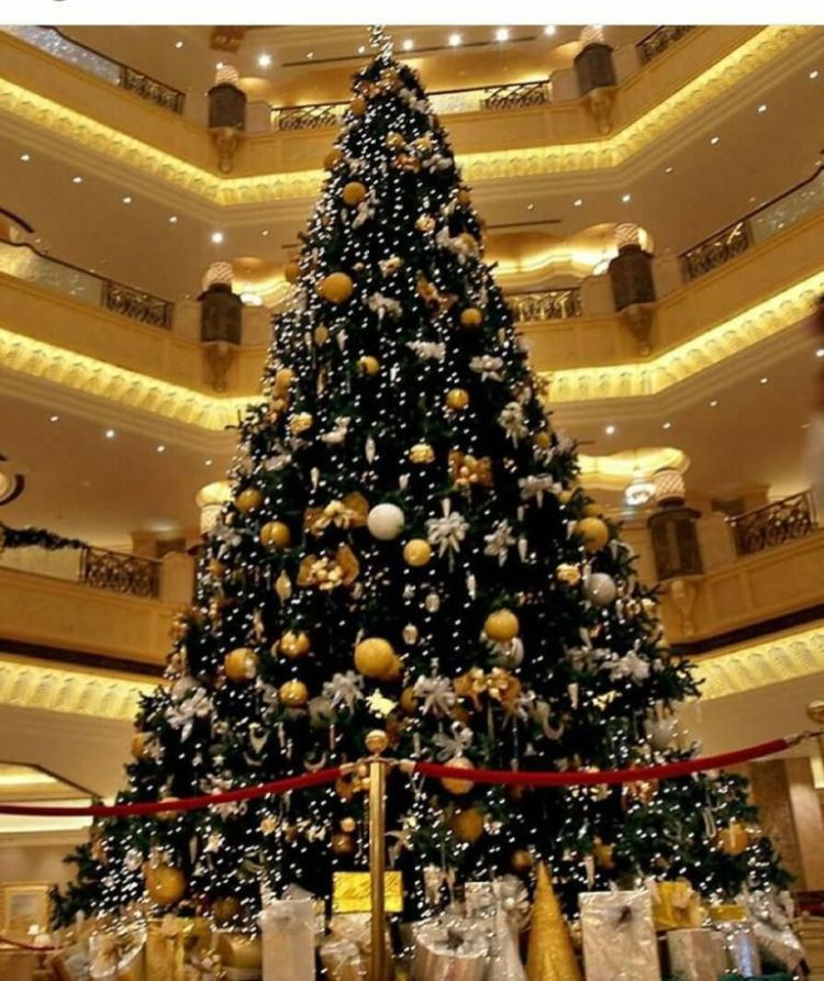 Big Christmas Tree Decorated With Gold Bells And Gifts In Hotel