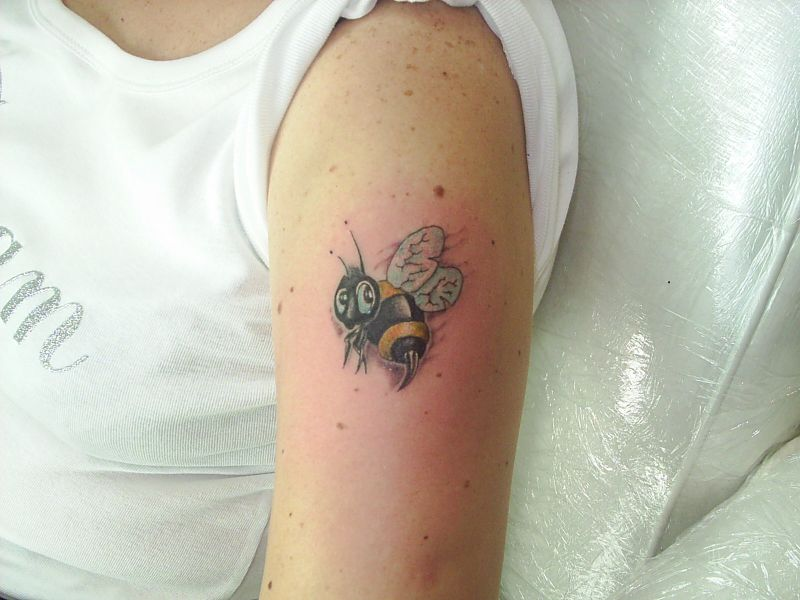Brillliant Black And Yellow Color Ink Bumblebee Tattoo On Muscles For Girls On Arm