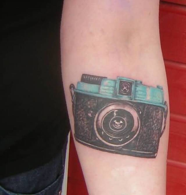 Fabulous Blue And Black Color Ink Camera Tattoo Design For Girls On Arm