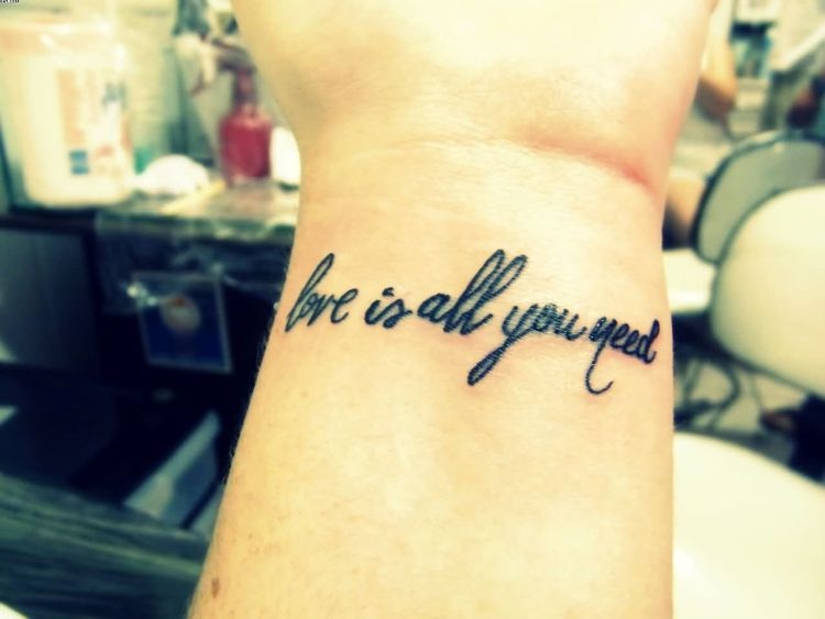 Great Quote Love Is All You Need Tattoo On Wrist With Black Ink