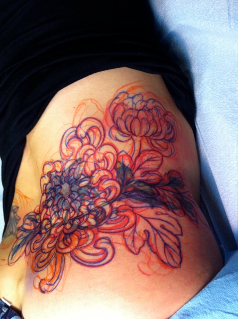 Impressive Yellow Red And Black Color Ink Chrysanthemum Tattoo On Lower Back For Girls