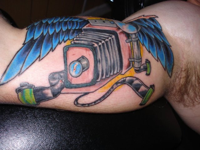 Mind Blowing Green Blue Black And Red Color Ink Camera With Wings Tattoo On Muscles For Boys