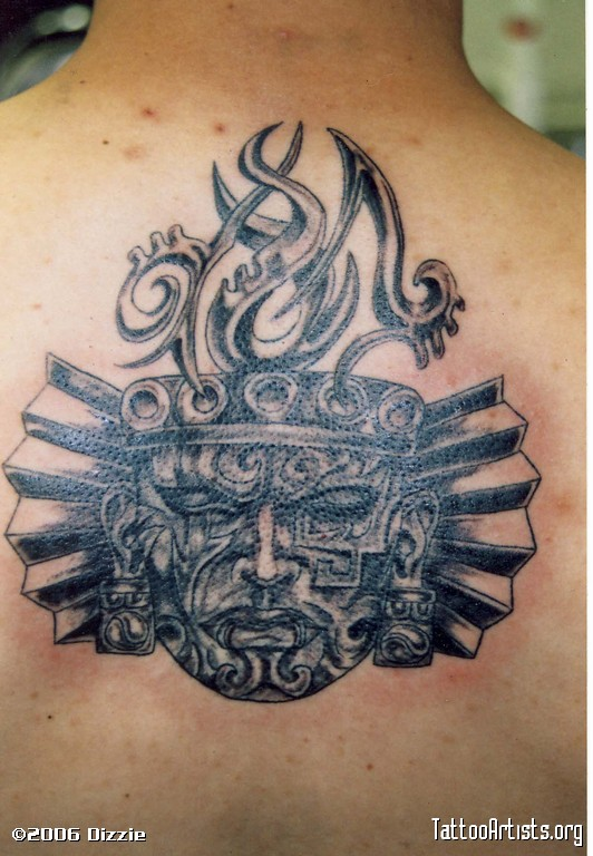 Nice Black Color Ink Aztec Face Tattoo On Upper Back For Boys