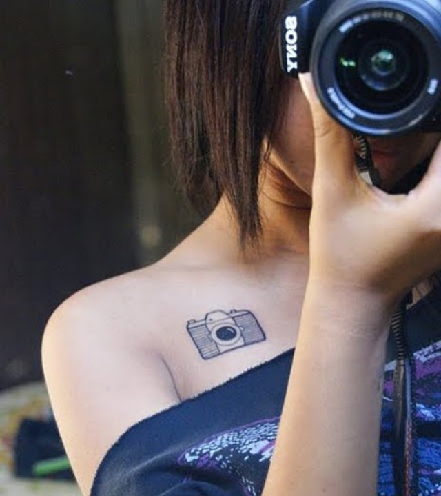 Nice Black Color Ink Tiny Camera Tattoo On Collarbone For Girls