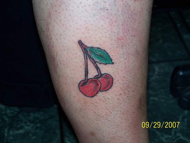 Nice Green And Red Color Ink Two Cherries Tattoo On Leg For Boys