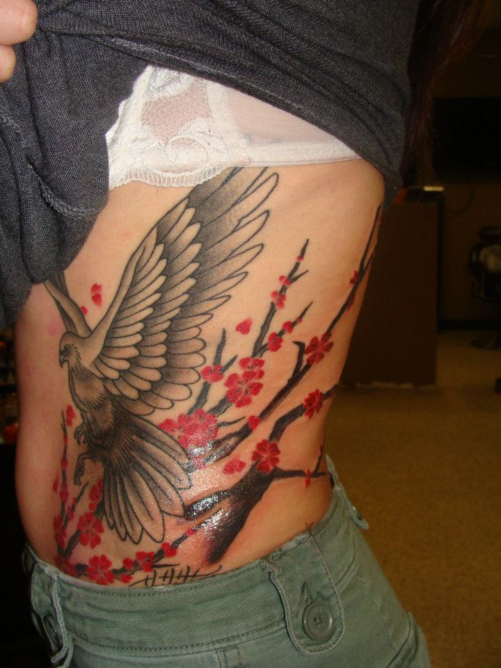 Realistic Black And Red Color Ink Asian Bird & Blossoms Tattoo On Rib Side For Girls