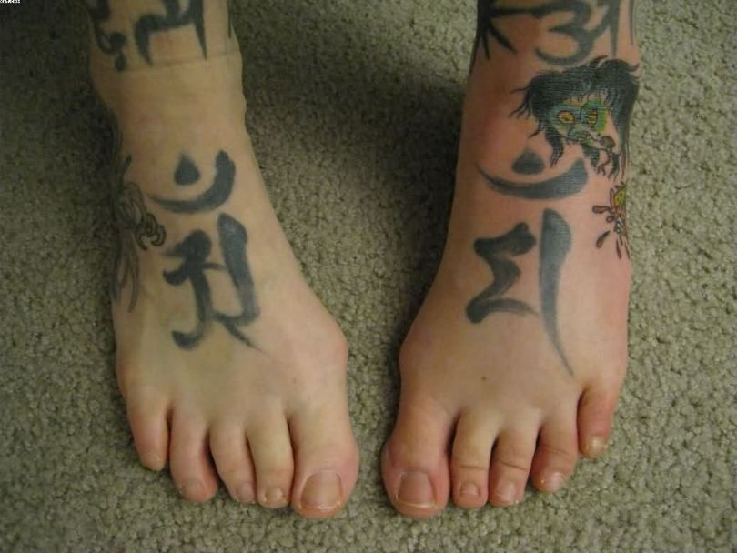 Simple Zombie Girl And Kanji Symbols Tattoos On Feet With Black Ink