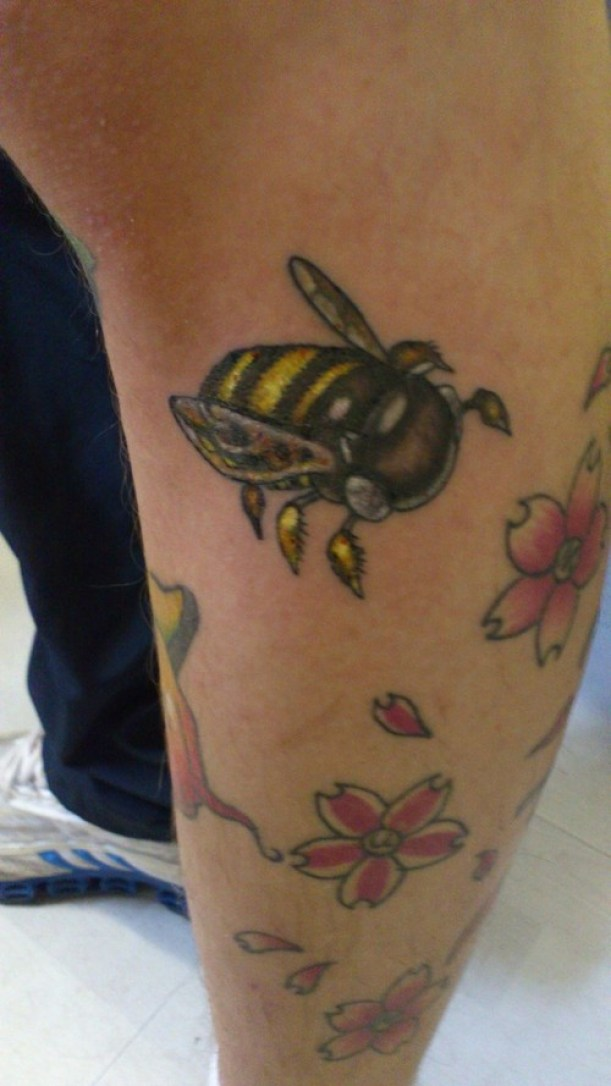 Superb Red Black And Yellow Color Ink Bumblebee Tattoo With Flowers On Leg For Girls