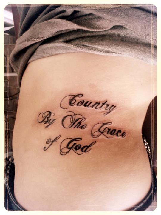 Trendy Black And Red Color Ink Country By The Grace Of God Tattoo On Rib Side For Girls