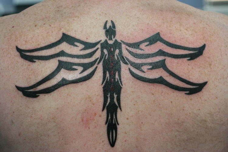 Superb Tribal Dragonfly Tattoo On Upper Back For Boys