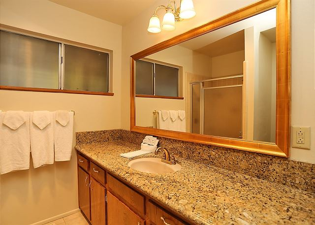 Large mirror with wooden frame and beautiful granite counter-top.