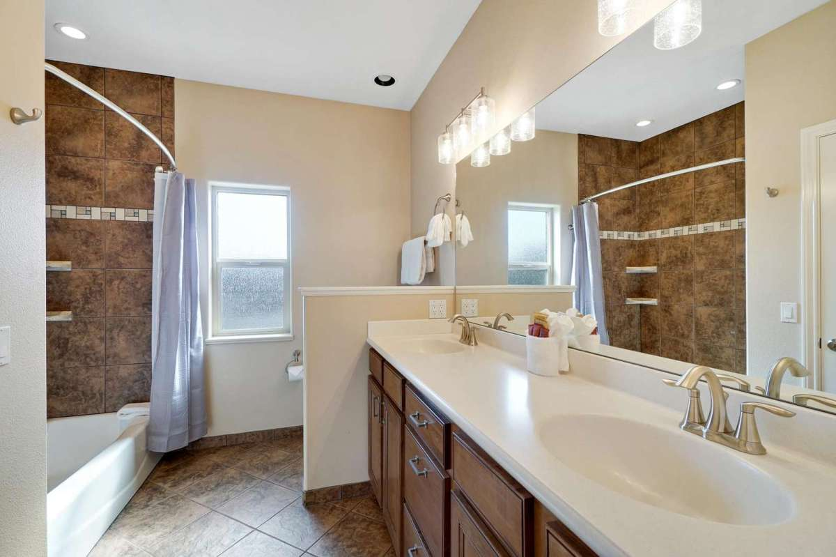 Hallway bathroom has a tub and double sinks