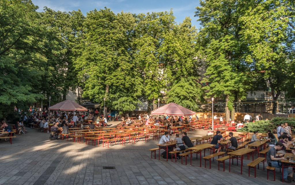 The picnic tables and shady trees of the Prater Garten in Berlin, Germany.