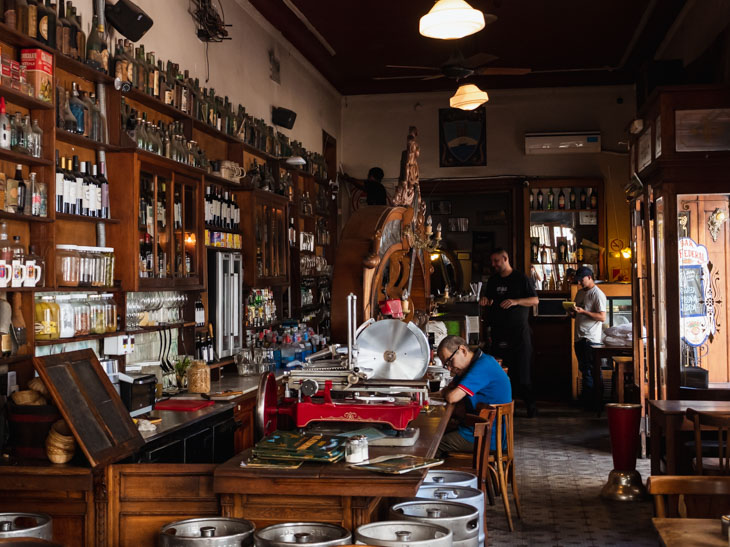 A man sits at the bar of an old mahogany bar in El Federal, Buenos Aires, Argentina