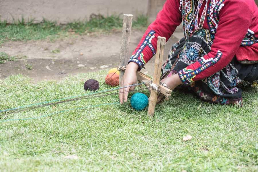 Peruvian textile weaving - Women establish the framework for their scarf