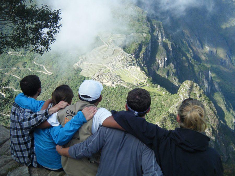 Inca Jungle Trail - Tourists embrace as they gaze at Machu Piucchu from afar.
