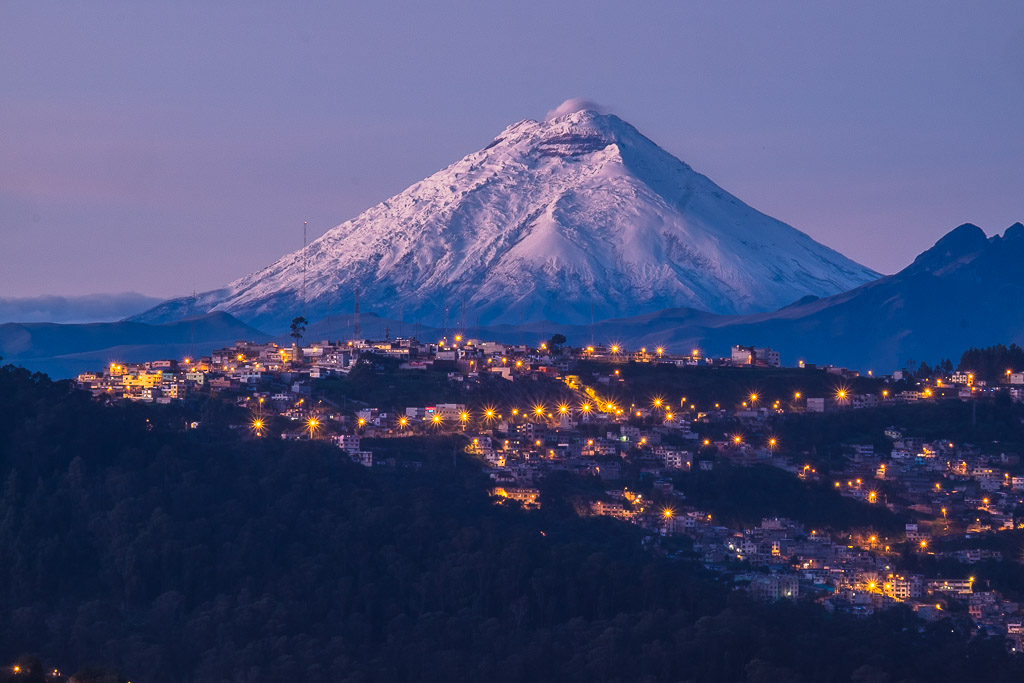Snow-capped Cotopaxi volcano surrounded by the city lights of Quito.