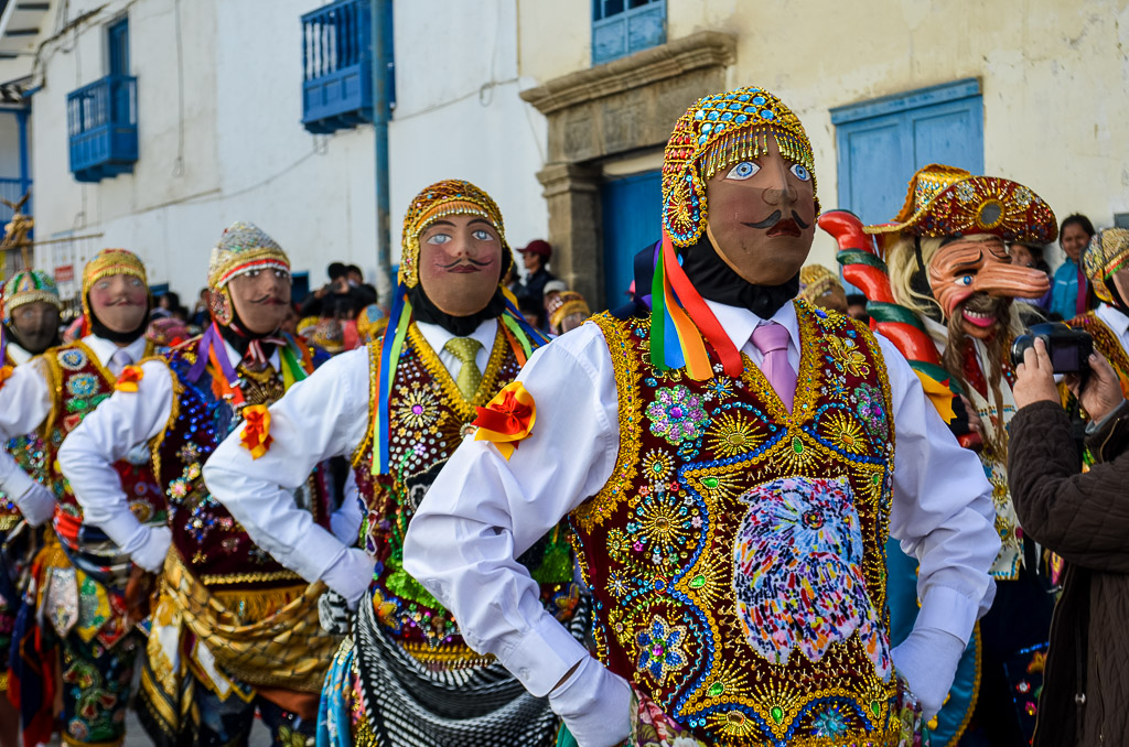 Performers in colorful costumes and masks at the Virgin del Carmen Festival