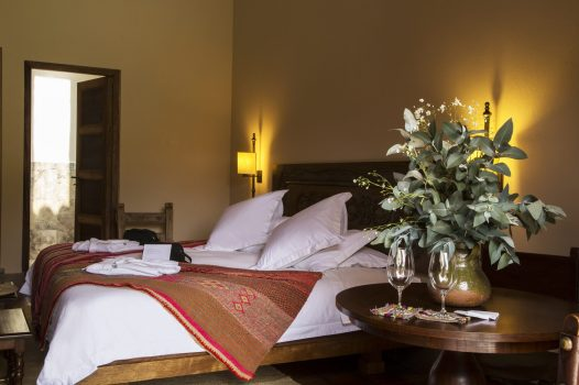 Luxury hotels in Sacred Valley - Bed and wine glasses in Urubamba Superior Deluxe suite, Inkaterra.
