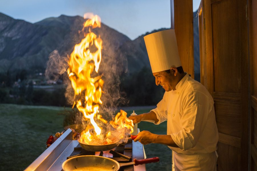 Luxury hotels in Sacred Valley - Chef with flaming pan during cooking classes at Inkaterra Hacienda.