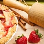 strawberry rhubarb pie with cinnamon sticks wooden rolling pin fresh strawberries on a light wood table and fresh rhubarb in the background tied with string
